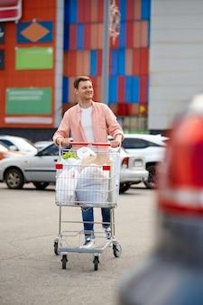 Молодой человек с тележкой на автостоянке супермаркета. счастливый клиент, несущий покупки из торгового центра, автомобили на заднем плане