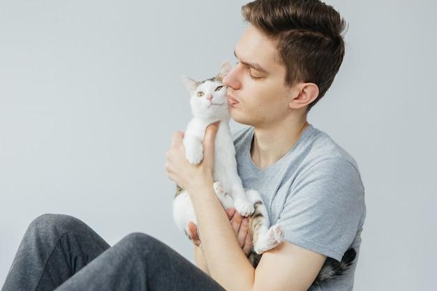 Молодой человек с кошкой на светло-сером фоне. любимое животное. мужчина держит кошку