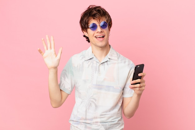 Young man with a cell phone smiling happily, waving hand, welcoming and greeting you