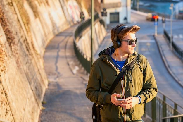 Молодой человек с мобильным телефоном на улице