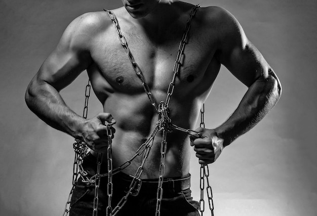 벌거 벗은 몸통과 회색 배경에 스튜디오에서 포즈를 취하는 강한 근육질의 몸에 체인을 가진 젊은 남자.
