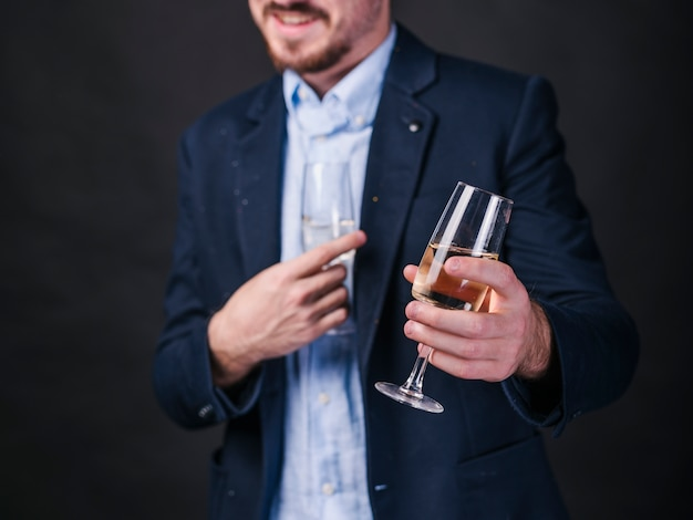 Young man with champagne glasses in hands