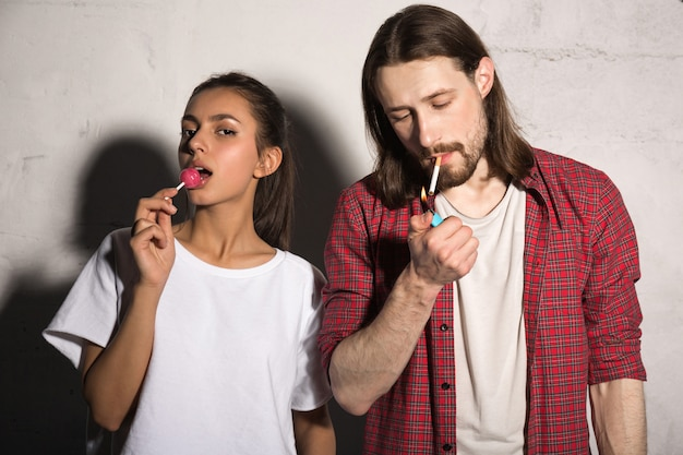 お菓子を食べてガールフレンドの近くのタバコを持つ若者