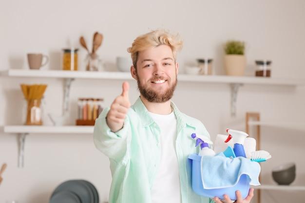 청소 용품 부엌에서 엄지 위로 보여주는 젊은 남자