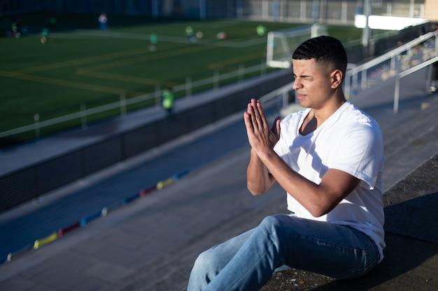 Молодой человек с закрытыми глазами сидит на трибуне стадиона во время молитвы