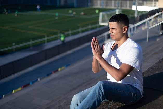 Young man with closed eyes sitting on stadium bleachers while praying