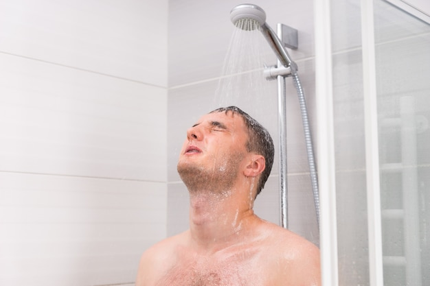 Young man with closed eyes taking a shower, standing under flowing water in shower cabin with transparent glass doors in the bathroom
