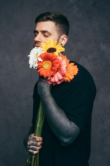 Young man with closed eyes and tattooed on his hand holding gerbera flower in hand