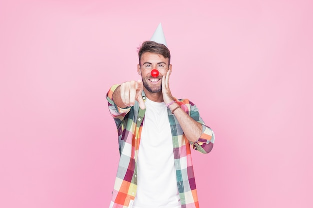 Young man with clown nose pointing his finger on pink background