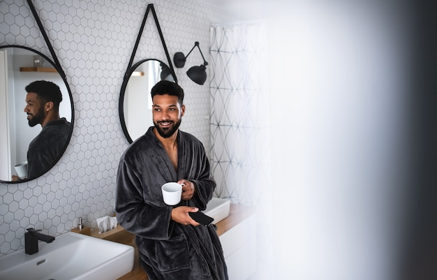 Young man with coffee and bathrobe indoors in bathroom at home, using smartphone.