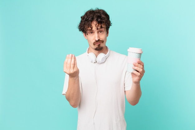 Young man with a coffee making capice or money gesture, telling you to pay