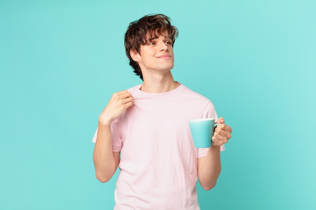 Young man with a coffee mug looking arrogant, successful, positive and proud