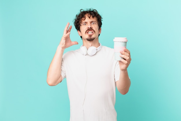 Young man with a coffee screaming with hands up in the air