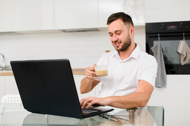 Young man with coffee smiling at laptop