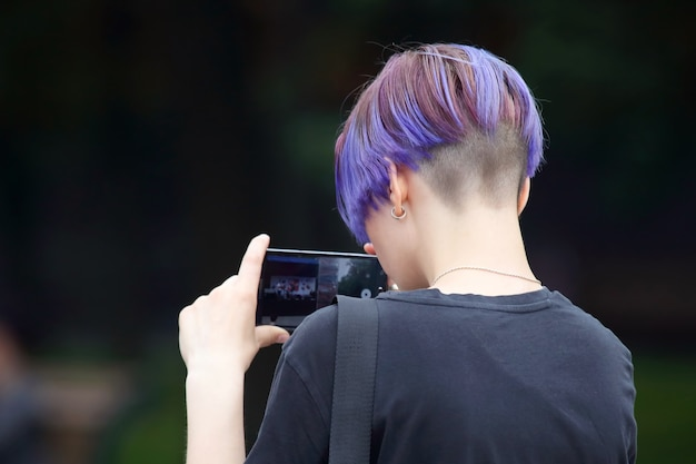 Young man with colored hair shoots a video using a smartphone event