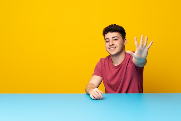 Young man with colorful wall and table counting five with fingers