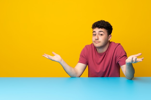 Young man with colorful wall and table having doubts while raising hands