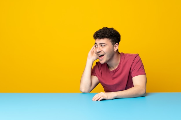 Young man with colorful wall and table listening to something by putting hand on the ear