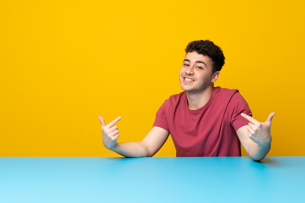 Young man with colorful wall and table proud and self-satisfied