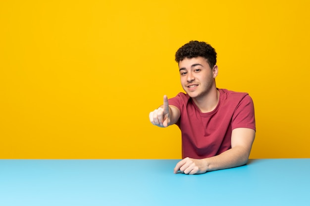 Young man with colorful wall and table showing and lifting a finger