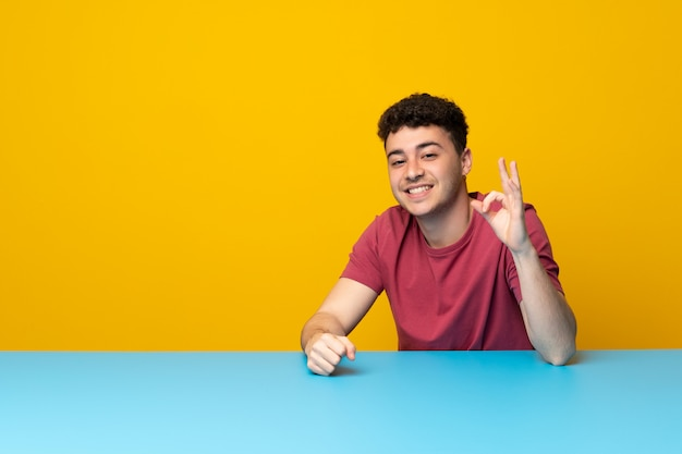 Young man with colorful wall and table showing ok sign with fingers