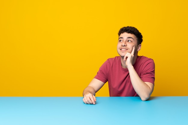 Young man with colorful wall and table thinking an idea while looking up