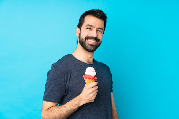 Young man with a cornet ice cream over blue laughing