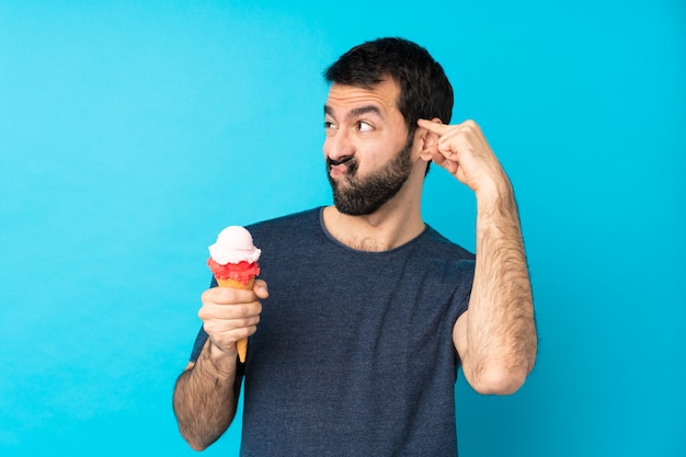 Young man with a cornet ice cream over blue making the gesture of madness putting finger on the head