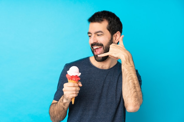 Young man with a cornet ice cream over blue making phone gesture. call me back sign