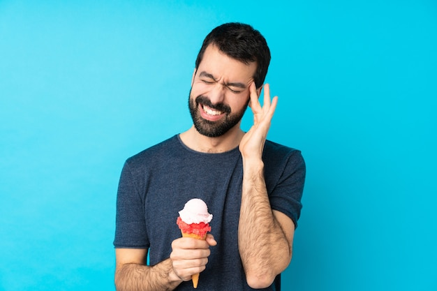 Young man with a cornet ice cream over blue with headache