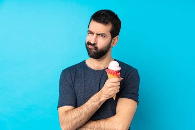 Young man with a cornet ice cream feeling upset