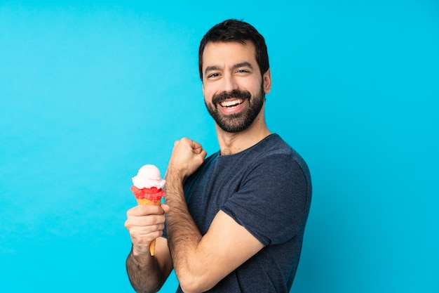 Young man with a cornet ice cream over isolated blue wall celebrating a victory