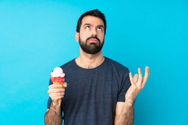 Young man with a cornet ice cream over isolated blue wall frustrated by a bad situation