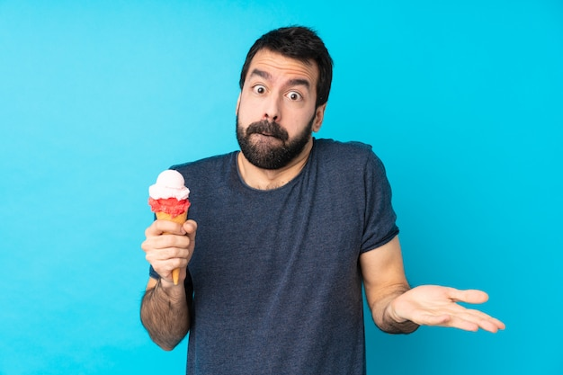Young man with a cornet ice cream over isolated blue wall having doubts while raising hands