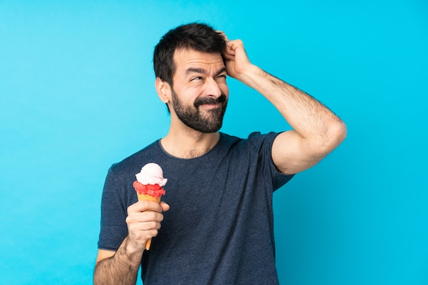 Young man with a cornet ice cream over isolated blue wall having doubts while scratching head
