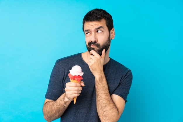 Young man with a cornet ice cream over isolated blue wall having doubts and with confuse face expression