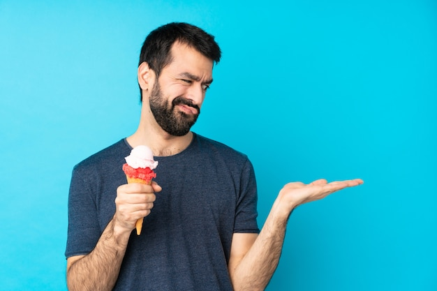 Young man with a cornet ice cream over isolated blue wall holding copyspace with doubts