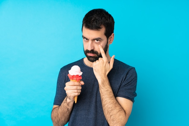 Young man with a cornet ice cream over isolated blue wall showing something