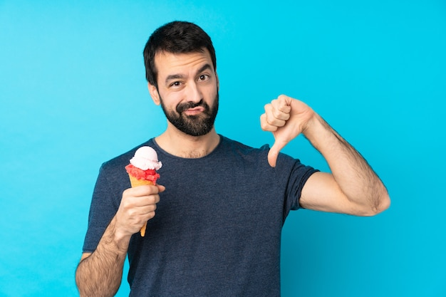 Young man with a cornet ice cream over isolated blue wall showing thumb down