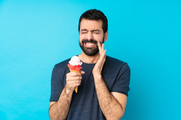 Young man with a cornet ice cream over isolated blue wall with toothache