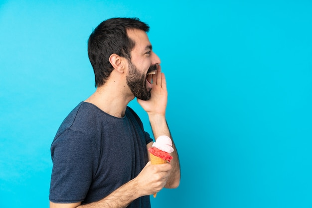 Young man with a cornet ice cream over isolated blue