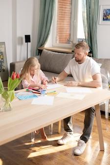 Молодой человек с мелком на чистом листе бумаги помогает своей милой маленькой дочери рисовать картину, сидя за деревянным столом в гостиной