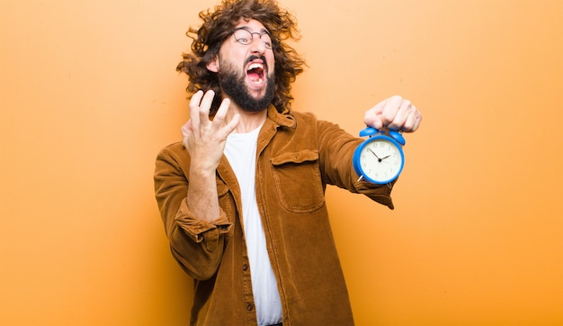 Young man with crazy hair in motion and an alarm clock