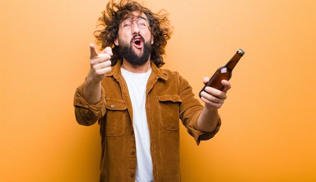 Young man with crazy hair in motion drinking a beer
