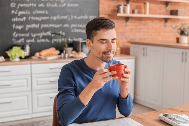 キッチンでホットコーヒーのカップを持つ若い男