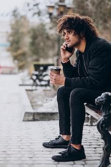 Молодой человек с вьющимися волосами пьет кофе и разговаривает по телефону