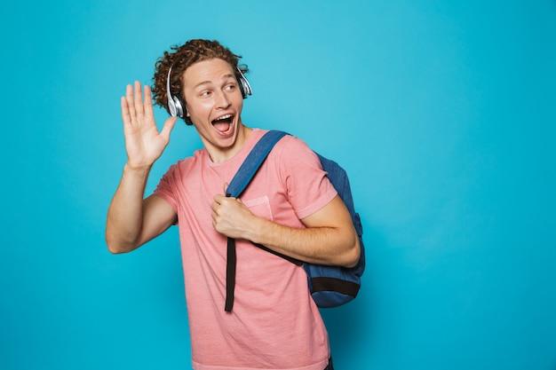 Молодой человек с вьющимися волосами, носить рюкзак, слушать музыку через наушники и махнув рукой в сторону