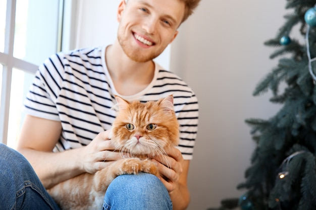 Young man with cute cat at home on christmas eve