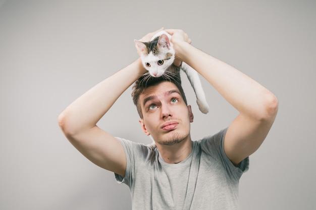 明るい背景にかわいい面白い猫と若い男