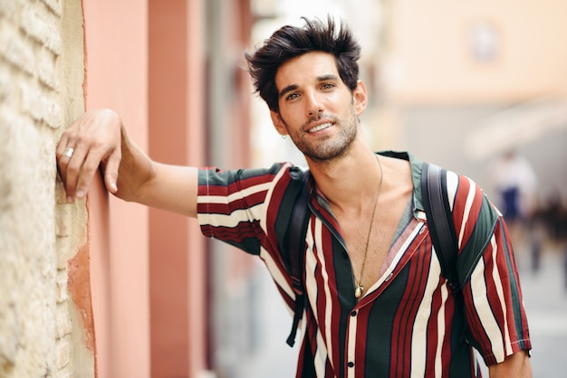 Young man with dark hair and modern hairstyle wearing casual clothes outdoors